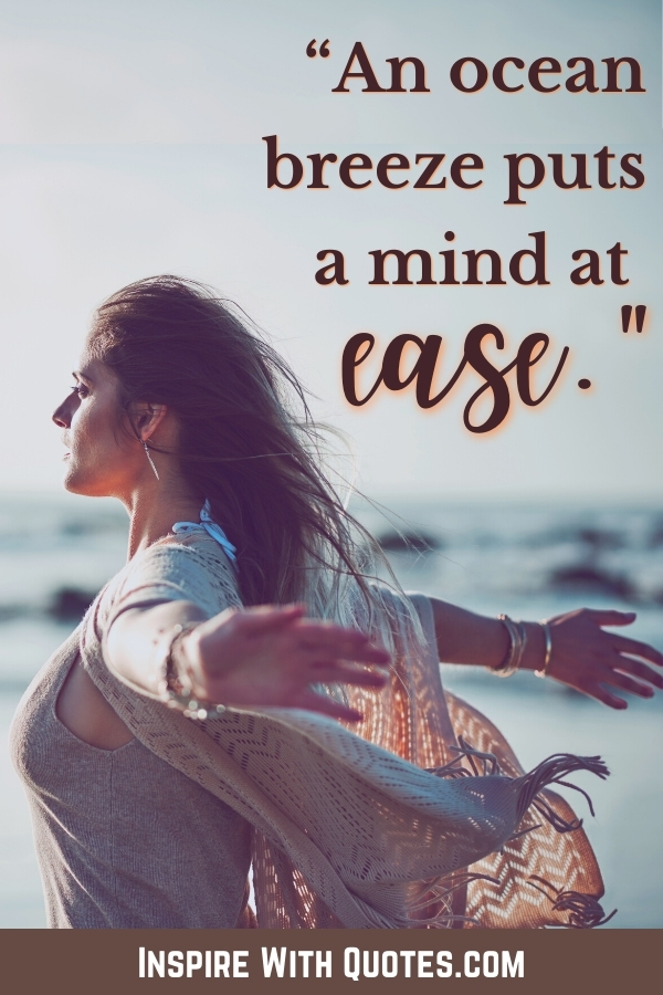 """woman staning next the ocean with hair flowing in the air and caption """"an ocean breeze puts the mind at ease"""""""